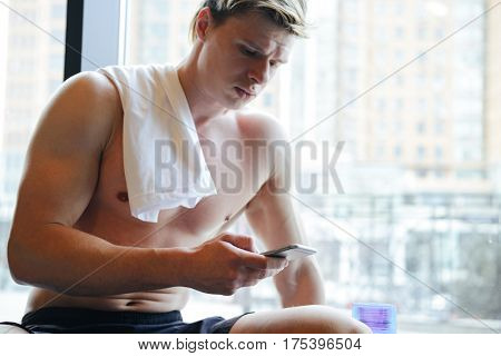 Atletic man with naked torso which sitting near the window and using smartphone