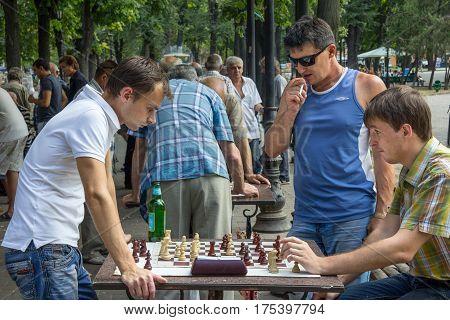 ODESSA UKRAINE - AUGUST 14 2015: Young men playing chess in a park of Odessa Ukraine