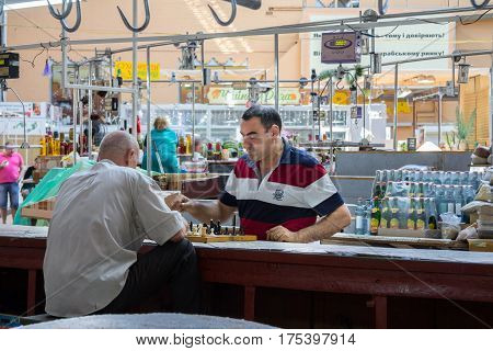 KIEV UKRAINE - AUGUST 17 2015: Butchers playing chess next to the meat they are selling inside Besarabsky market one of the iconic markets of Kiev