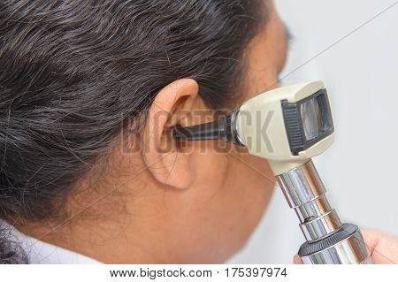Closeup doctor Examining Patient's Ear With Otoscope