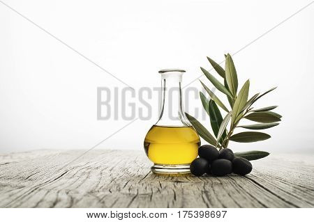 Olive oil with black olives and branch on wood