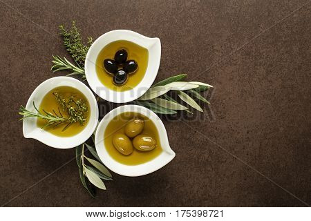 Olive oil with fresh herbs on brown background