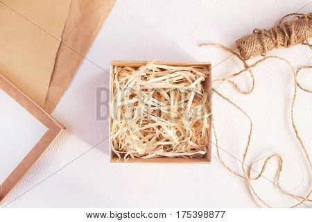 Gift packing process with craft box and brown paper on light background