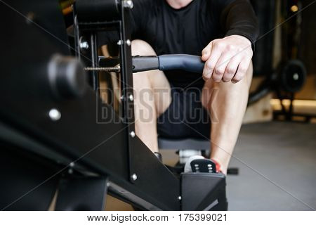Cropped image of Muscular man which using rowing machine in gym