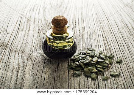 Dark pumpkin oil with seeds on wooden background