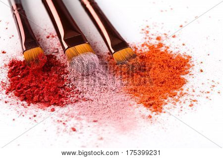 Makeup brushes with blush or eyeshadow of pink, red and coral tones sprinkled on white. Make up and female cosmetics background