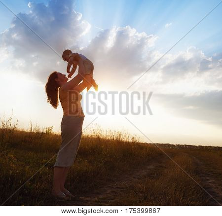 Happy mother with baby boy in the meadow evening light