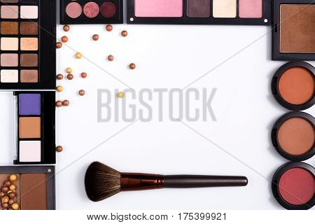 Makeup cosmetics, brush and other essentials frame on white background. Top view, flat lay with copy space. Beauty tools palettes collection, lipstick, eyeshadow, blush, foundation and more