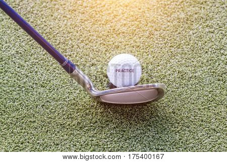 Practice golf ball and golf club on green golf course with warm sunlight in background beginner concept.