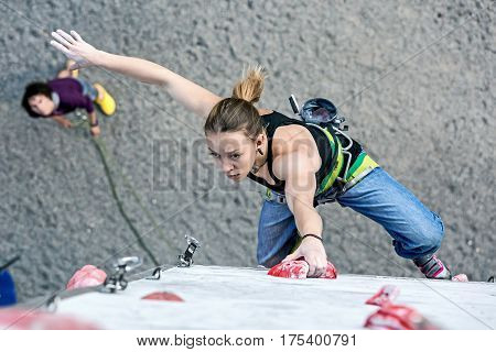 Cute female Athlete hanging on climbing Wall making hard move and belaying Partner watching from below