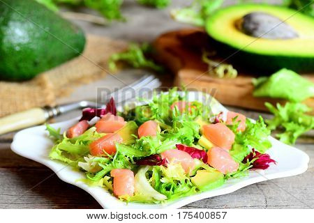 Salmon, avocado and mixed lettuce salad recipe. Easy salad with salmon slices, fresh avocado and lettuce leaves mix on a plate. Avocado, fork on a vintage wooden table. Closeup