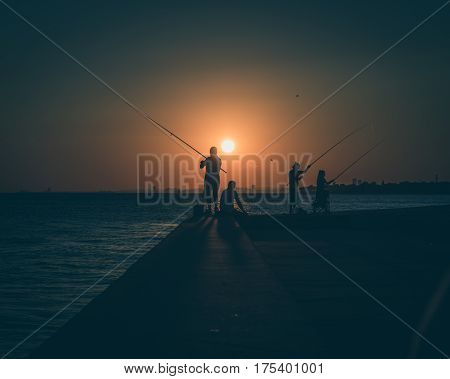 Silhouettes Of Fishermen By The Sea At Sunset