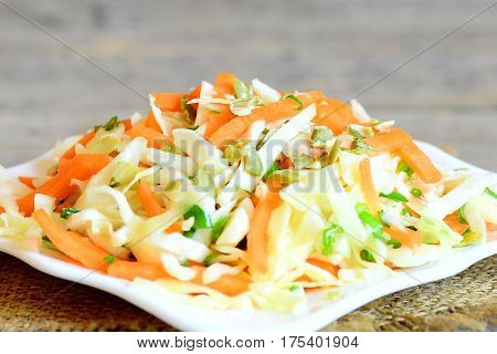 Easy homemade coleslaw salad. Tasty coleslaw salad with carrots, green onion and pumpkin seeds on a plate and on a wooden table. Fresh vegetable meal. Closeup