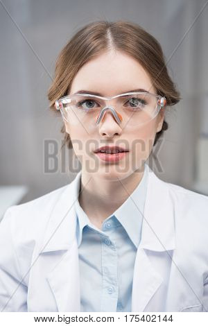 Portrait of young professional female scientist in protective eyewear