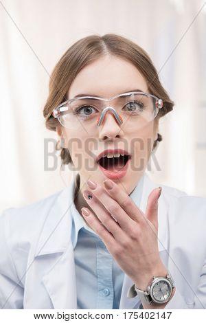Surprised professional female scientist in protective eyewear