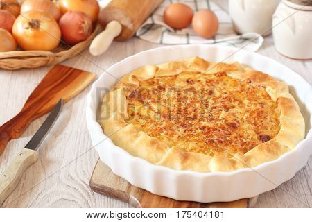Onion cheese pie on wooden chopping board and ingredients