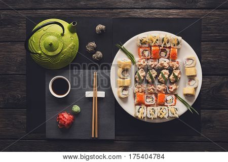 Japanese food restaurant, sushi maki gunkan roll platter. Teapot and black slate plate with chopsticks, ginger, soy, wasabi. Top view with copy space on rustic wood background. Vintage filter