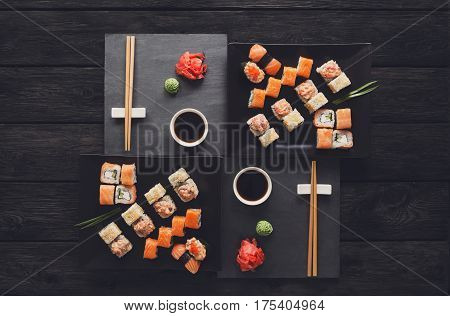 Japanese food restaurant, salmon sushi maki gunkan roll platter. Set for two with chopsticks, ginger, soy, wasabi. Top view on rustic wood background and black slate plates. Vintage filter