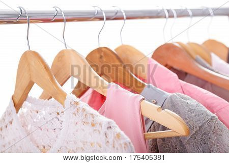 gray and pink womens clothes on wooden hangers on a rack on white background. woman's wardrobe