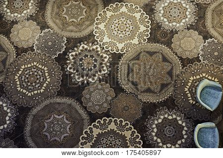 Beautiful brown flower motifs carpet and two bluish chairs in hotel lobby, seen from above.