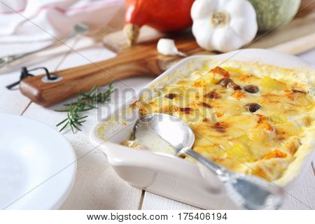 Pumpkin gratin with cheese and mushroom on ceramic dish