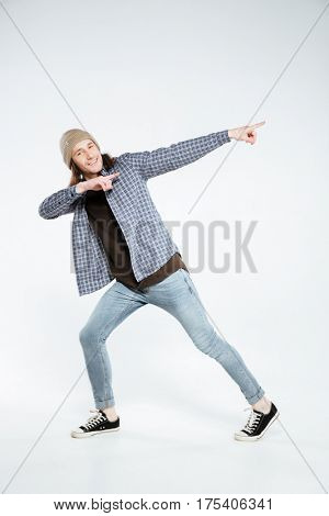 Vertical image of Smiling hipster which pointing away and looking at camera. Isolated gray background