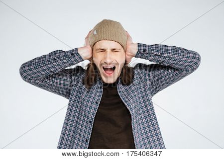 Screaming hipster which closed eyes and covering his ears. Isolated gray background
