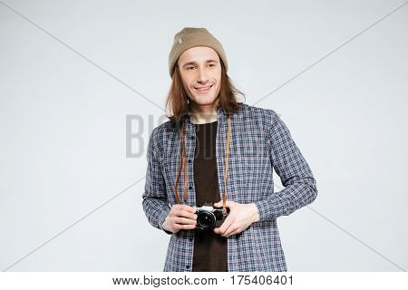 Smiling hipster in shirt and hat which holding retro camera and looking away