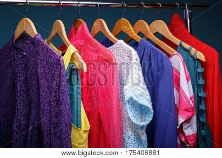 colorful womens clothes on wood hangers on rack on blue background. women's closet closeup