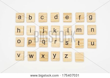 Lowercase alphabet letters on wooden tiles, on white background