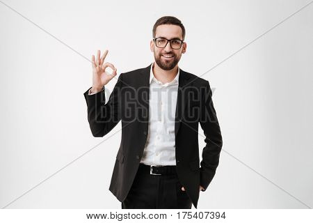 Image of attractive happy young bearded businessman wearing glasses standing and posing over white background make okay gesture.