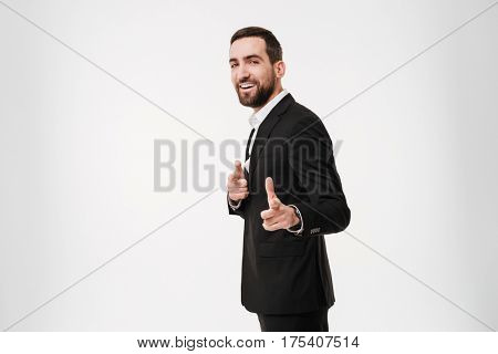 Photo of smiling young businessman standing and posing over white background and pointing at camera. Looking at camera.