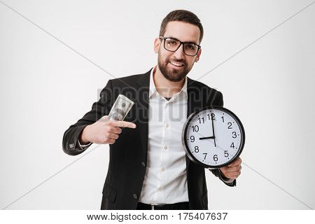 Image of young bearded businessman over white background holding money and pointing to watch.