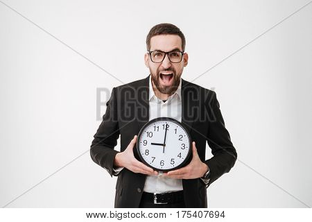 Image of young screaming bearded businessman over white background holding watch.