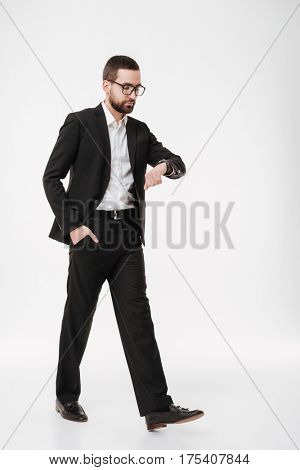 Photo of serious young bearded businessman posing over white background while looking at watch.