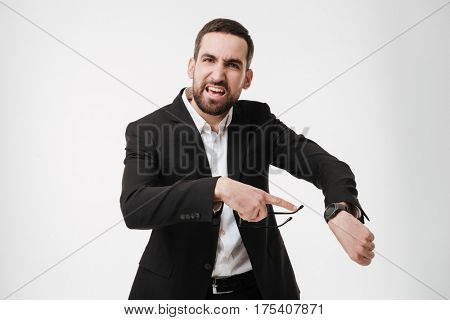Photo of angry young bearded businessman posing over white background while showing his watch. Looking at camera.