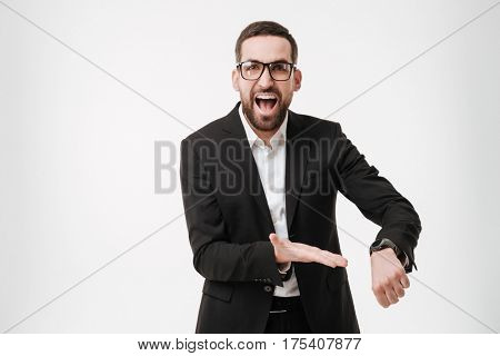 Photo of screaming young bearded businessman posing over white background while showing his watch. Looking at camera.