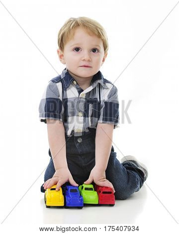 An adorable 2-year-old looking up from his 4 toy vehicle lineup.  On a white background.