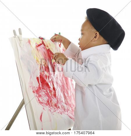 Profile of an adorable preschool artist wearing a French beret and white smock, putting the finishing touches on his water color painting.  On a white background.