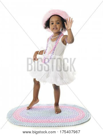 An adorable barefoot two year old waving hello (or good-bye) in her white petticoat and pastel pearls and hat.  On a white background.