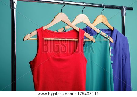 colorful women's shirts on wood hangers on rank on blue background. RGB concept