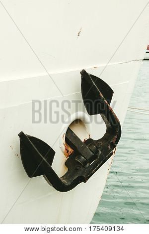Big old black anchor on a white boat