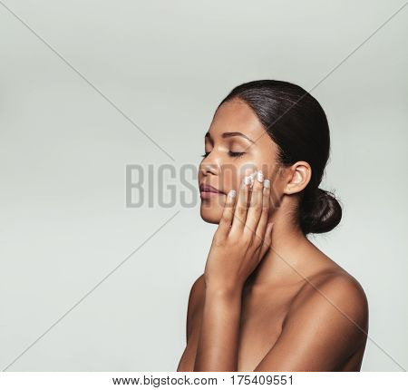 Beautiful young woman with eyes closed while applying moisturizer to her clean face. Close up portrait female model applying face cream against grey background.