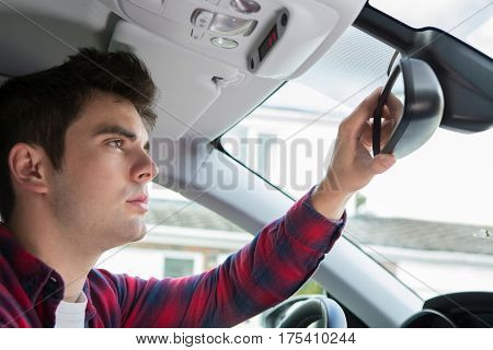 Young Male Driver In Car Checking Rear View Mirror