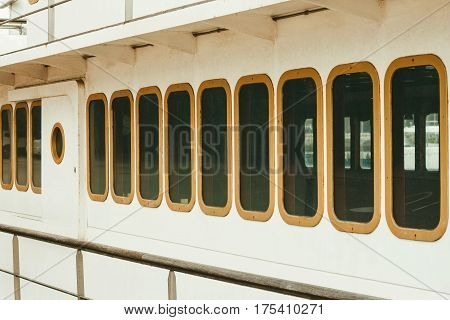 Old white metal ship with portholes and various marine equipment