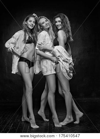 Three beautiful women in black erotic lingerie on white studio background. black and white photo