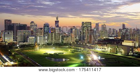 defocused and panorama background of Bangkok cityscape with golf course in nighttime