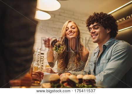 Couple eating burgers and drinking beer at home.
