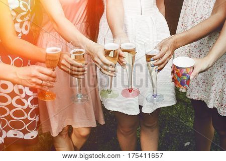 Hands Of Woman Holding Colorful Glasses And Toasting Champagne At Joyful Party In Summer Park, Brida