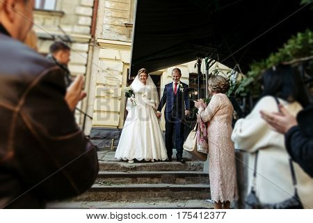 Beautiful Gorgeous Blonde Bride And Happy Stylish Groom Under Guests Cheering And Applauding, Offici